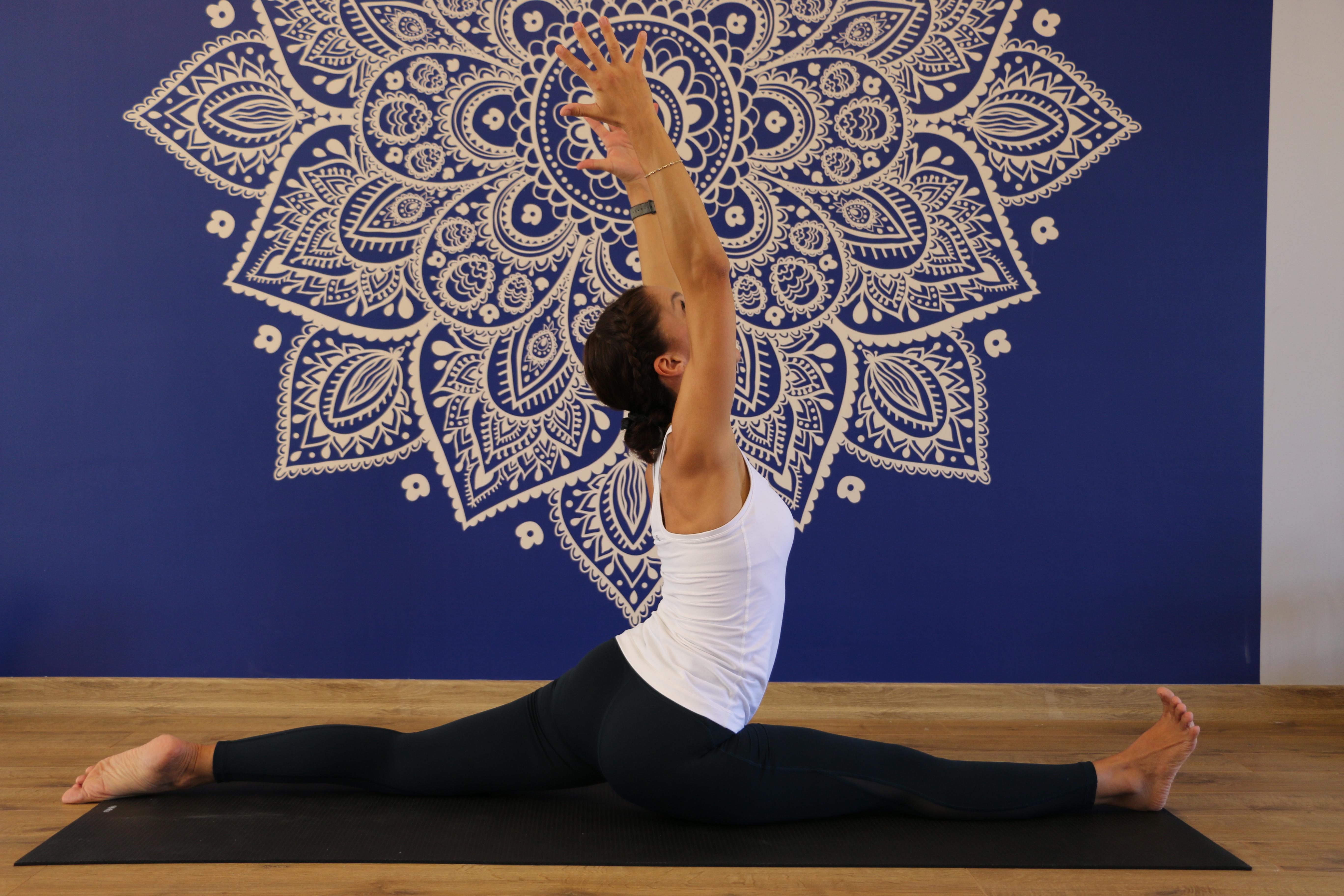bacaklarını açmış bir yoga yapan kadın